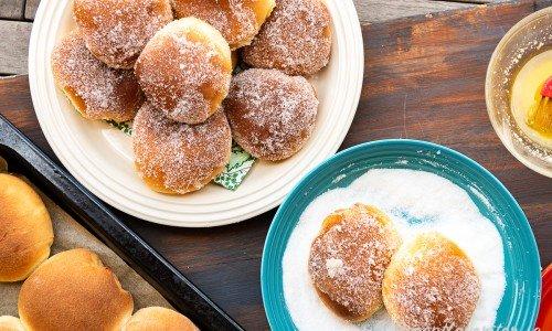 Sockerbullar med vaniljfyllning på fat och två som vänds i socker
