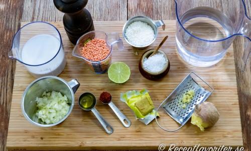 Ingredienser till soppan - kokosmjölk, hackad lök, röda linser, olja, röd currypasta, lime, kokosflingor, grönsaksbuljong, färsk ingefära, vatten, svartpeppar och flingsalt.