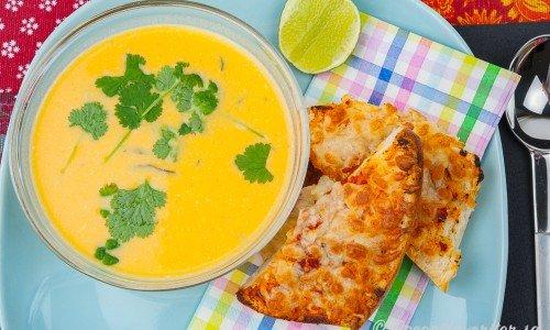 Sötpotatissoppa i soppskål med lime och färsk koriander serverad med matiga pizzamackor.