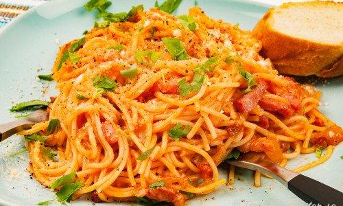 Spagetti med bacon, lök och ketchup på tallrik