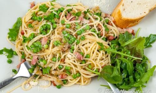 Spagetti med bacon och ärtor på tallrik