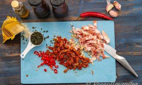 Strimlad bacon, hackade soltorkade tomater, vitlök och chili på skärbräda.