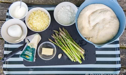 Jäst pizzadeg i bunke samt ingredienser som sparris och vitlök