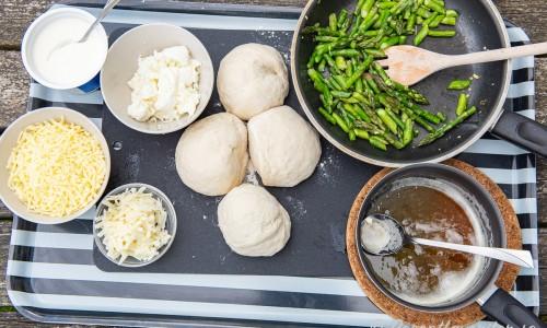 Ingredienser till sparrispizzan: riven mozzarella, créme fraiche, riven pecorino, färsk mozzarella, portionsbitar av deg, sparris fräst i olivolja och vitlök; samt brynt smör.