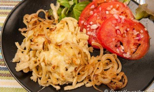 Spätzle gratinerad med riven ost med brynt lök, tomat- och grönsallad.