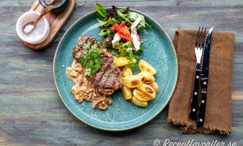 Stekt ryggbiff med kantarellsås, klyftpotatis och sallad på tallrik.