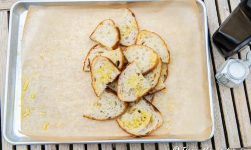 Skivat surdegsbröd blandas med olivolja samt flingsalt på bakplåtspapper.