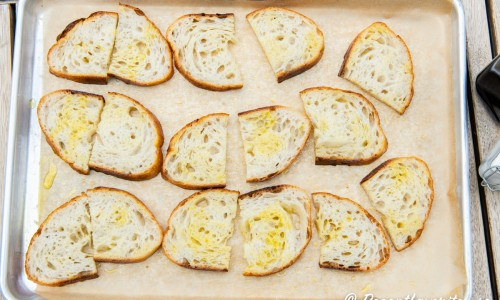 Sprid ut brödet på bakplåtspapper och rosta i ugnen.