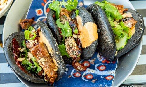 Svarta bao bullar fyllda med grillad fläskkarré, sås, jordnötter och grönt.