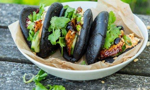Svarta bao bullar fyllda med grillad tempeh, sås, jordnötter och grönt.