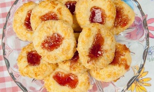 Syltkyssar med mandelmassa i degen samt toppade med vinbärsgelé och kokos på fat.