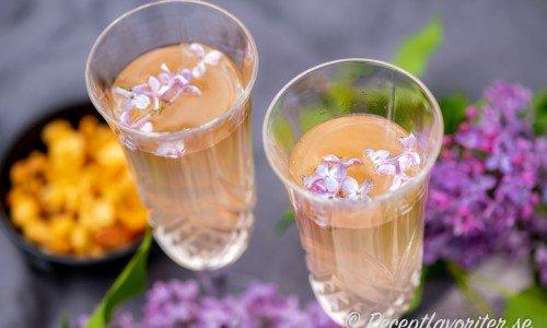 Två bubblande glas Syren Prosecco garnerade med syrenblommor.
