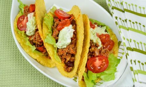 Tacosskal med köttfärs, guacamole, tomat, isbergssallad och bönor.