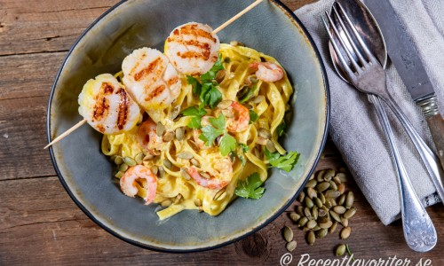 Grillade pilgrimsmusslor och handpillade räkor med pasta serverat i djup tallrik