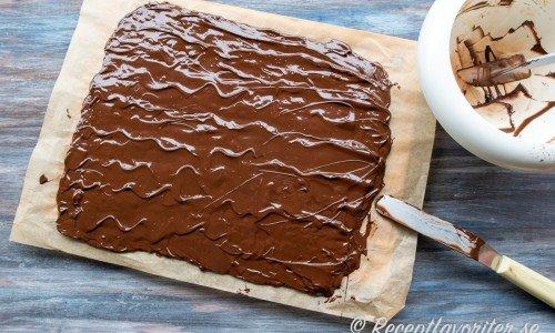 Den tempererade chokladen bres ut över som chokladöverdrag på fudgerutor.