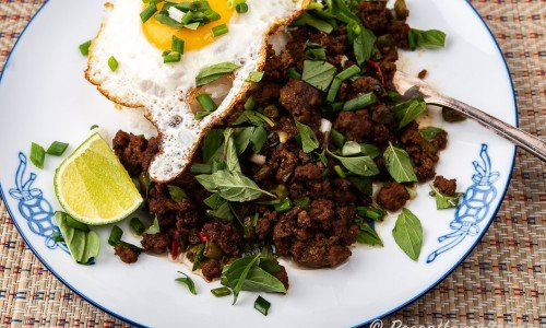 Thailändsk köttfärsröra med stekt ägg, ris och lime på tallrik