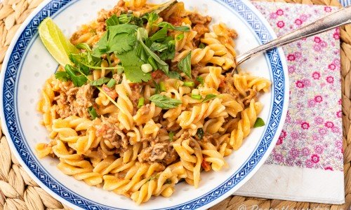 Thailändsk köttfärssås serverad med pastaskruvar, lime och färsk koriander på tallrik