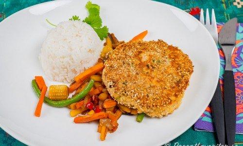 En thailändsk krabbkaka serverad med wokade grönsaker, ris och färsk koriander.