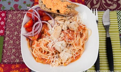 Pasta - här spagetti - med tomatsås, kyckling och riven parmesan.