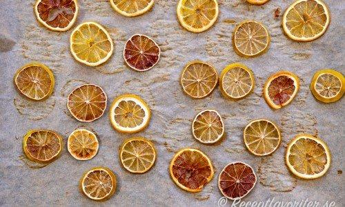Citrus som citron och lime i tunna skivor som får torka på bakplåtspapper.