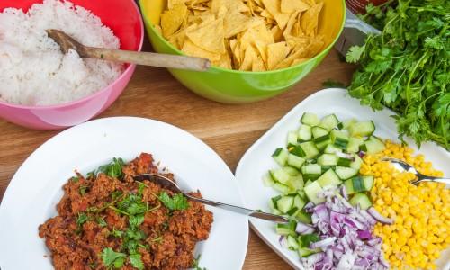 Kokt ris, tacochips, vegetarisk texmex-färs med sojafärs, gurka, rödlök, majs och färsk koriander samt chilisås sriracha.