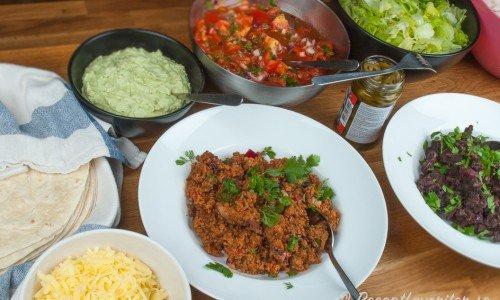 Varma tortillabröd, guacamole, tomatsalsa, isbergssallad, riven ost, tacofärs och stekta mosade svarta bönor.