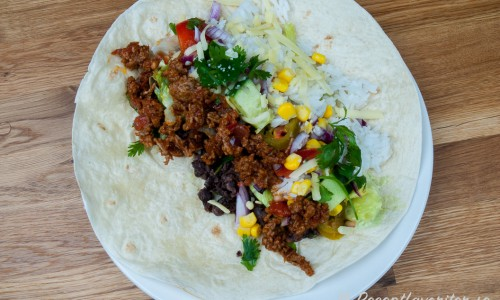Fyll tortillabröden med guacamole, köttfärsröra, svarta steka bönor, majs, rödlök, isbergssallad, jalapenos, färsk koriander, majs, ris och tomatsalsa samt het chilisås.