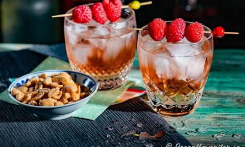 Tranbärsdrinkar med vodka och persikolikör toppade med is och Schweppes Russchian i glas garnerade med färska hallon.