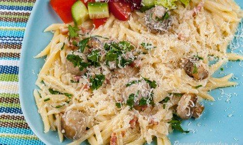 Trofie pasta med bacon, svamp och grädde på tallrik med sallad och riven parmesan.