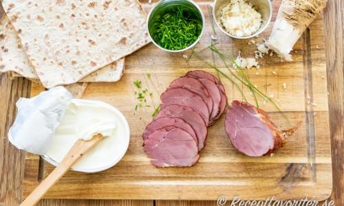 Ingredienser till klämmorna: tunnbröd, färskost, hackad gräslök, rökt vildsvinsstek och pepparrot.