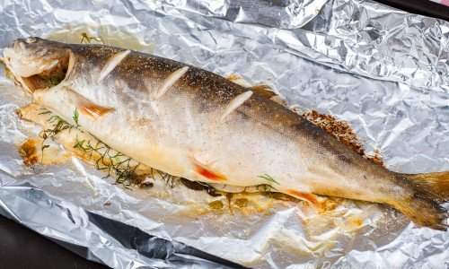 Ugnsbakad hel fisk på folie och ugnsplåt