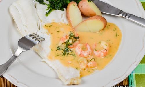 Ugnsbakad torsk med skaldjurssås, kokt potatis och spenat på tallrik