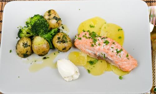 Ugnsstekt fylld lax på skivade gulbetor, örtslungade potatisar och broccoli samt en klick crème fraiche
