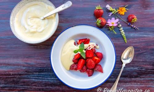 Vaniljsåsen blandad med lite vispad grädde och serverad med färska jordgubbar.