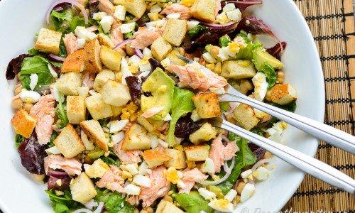 En laxsallad med varmrökt lax, avokado, kokt ägg, grönsallad, kikärtor, rödlök och krutonger.
