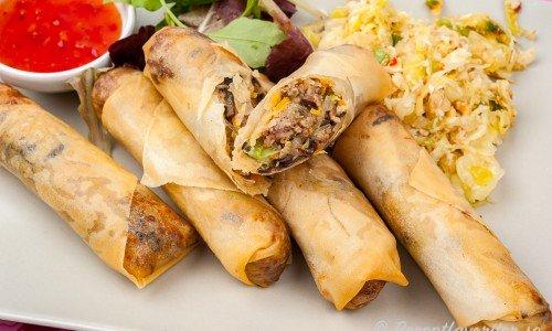 Vårrullar med köttfärs serverade med dippsås, grönsallad och vitkålssallad.