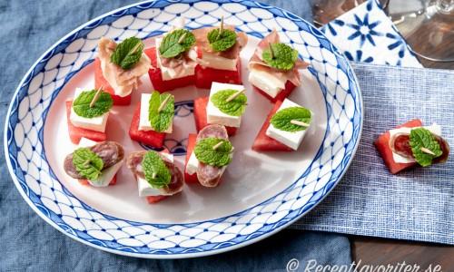 Tilltugg med vattenmelon i tärningar på tandpetare serverade på fat