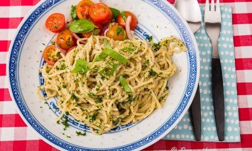 Vegan pasta med solrospesto serverad på tallrik med tomatsallad