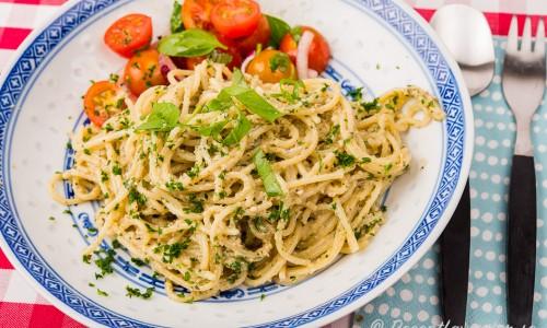 Solrospeston blandad med spagetti och serverad på tallrik med tomatsallad.