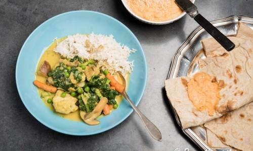 Vegansk gryta med grönsaker och curry serverad med ris, bröd och paprikahummus.