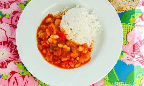 Vegetarisk gryta med vita bönor och paprika serverad med ris i tallrik