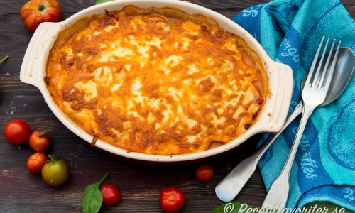 Grekisk potatisgratäng är en variant på moussaka med skivad potatis, aubergine, tomatsås och ostsås med fetaost. Tillbehör och sås i ett.