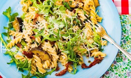 Vegetarisk pasta på tallrik garnerad med riven ost och ruccola