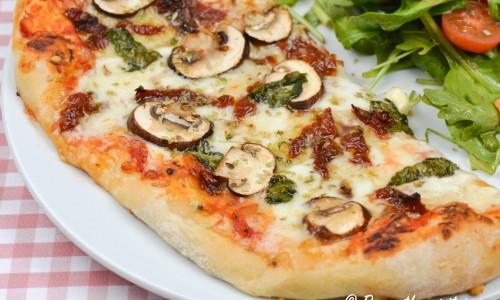 Vegetarisk pizza med soltorkad tomat, champinjoner och färsk basilika.