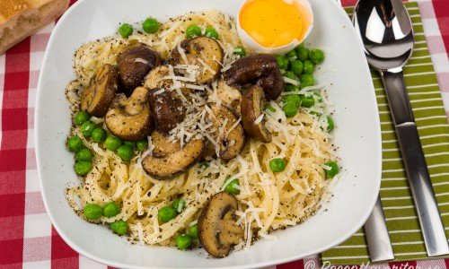 Vegetarisk spagetti eller pasta Carbonara med svamp - här skogschampinjon - grädde, gröna ärtor, svartpeppar, parmesan och äggula.