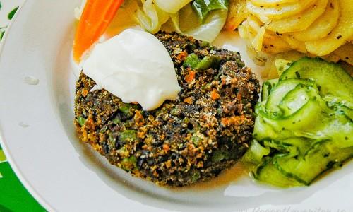 Vegetariska biffar med svarta bönor med tillbehör på tallrik
