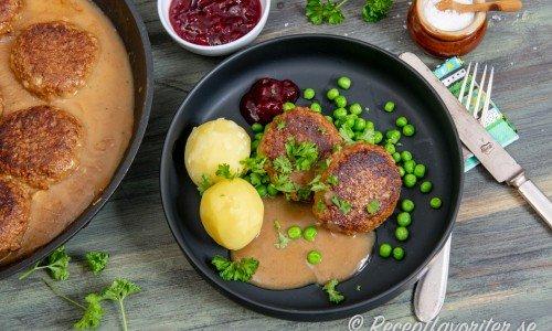 Sojafärsbiffarna serverade på tallrik med kokt potatis, gröna ärtor, sås, lingon och hackad persilja.