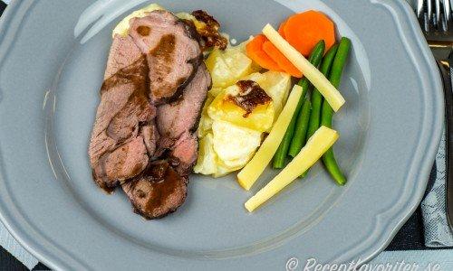 Viltstek i skivor med sky- och rödvinssås, potatisgratäng och kokta grönsaker.