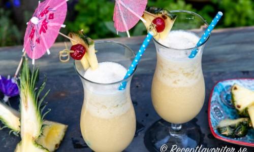 Garnera dina Virgin Colada med en bit färsk ananas, maraschino körsbär på tandpetare instucken i ananasen samt ett drinkparaply och sugrör.