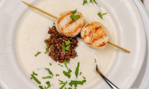 Vit bönsoppa med pilgrimsmusslor på spett garnerat med bladpersilja